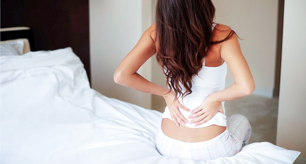 woman with backache sitting on mattress edge