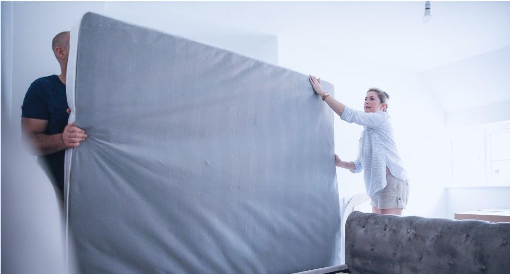 men and women rotating the mattress