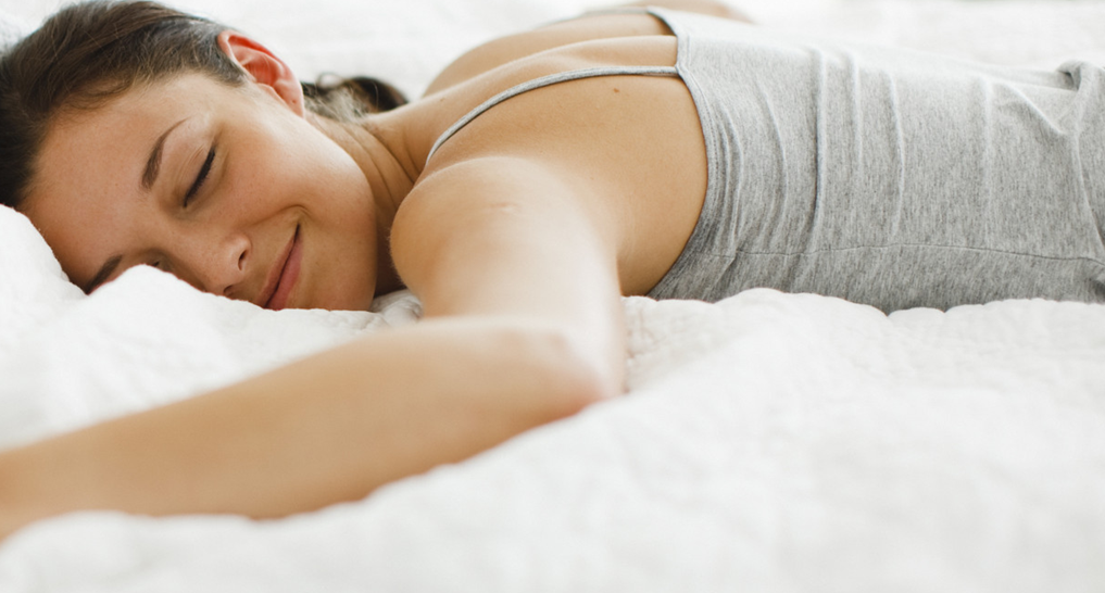 Image of someone sleeping happily in bed
