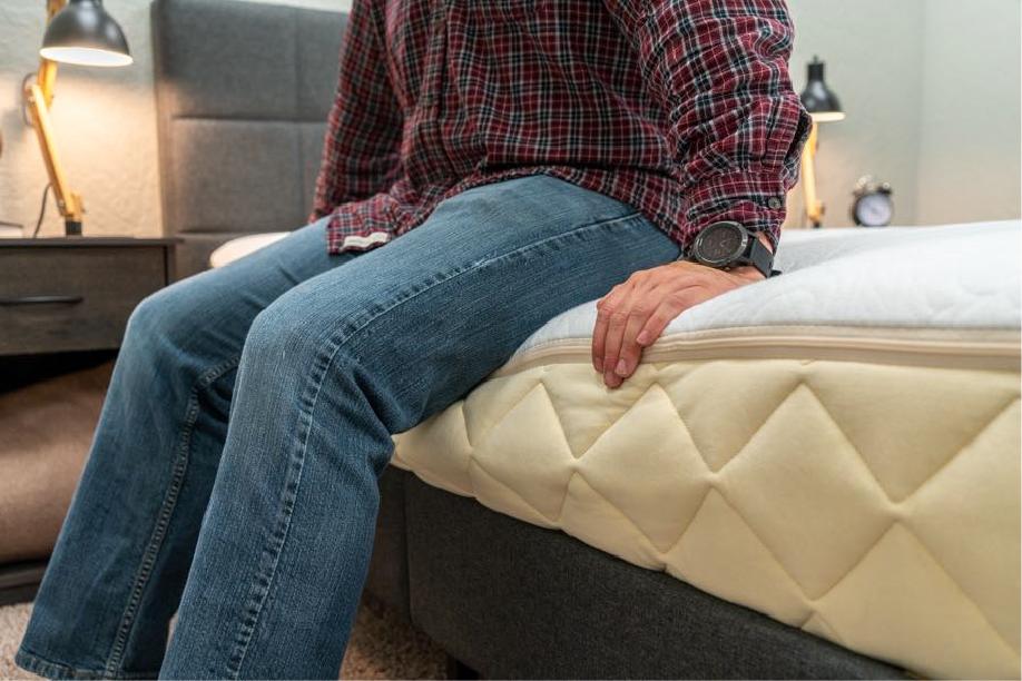 Person sitting on mattress